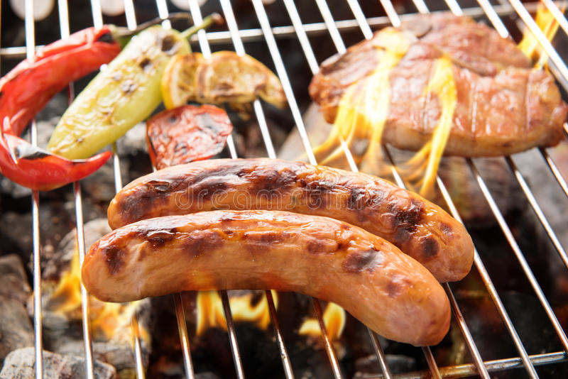 Worstvarkensvlees en karbonadelapje vlees op een vlammende BBQ grill stock afbeeldingen