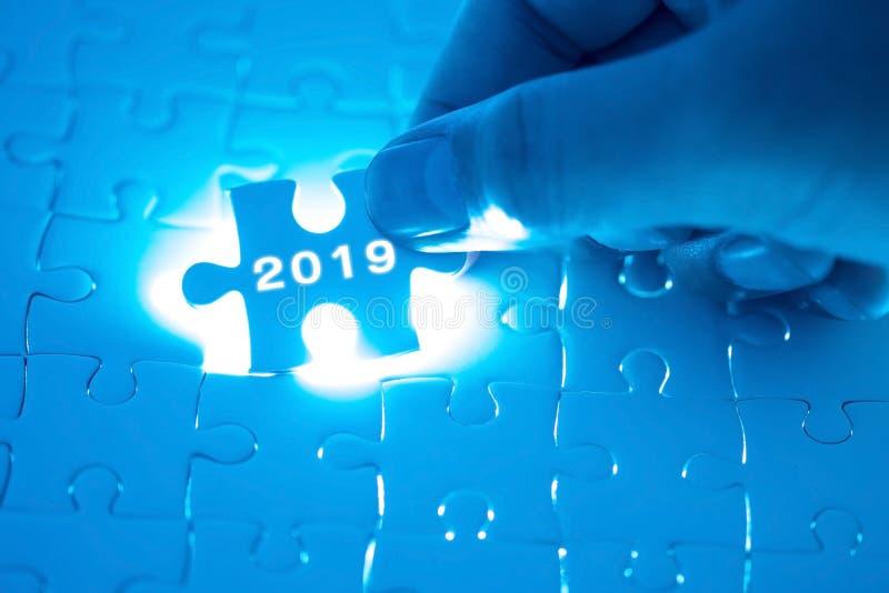Wort 2019 auf Puzzlen Geschäftsmannhände, die weißes puzz halten lizenzfreie stockfotografie