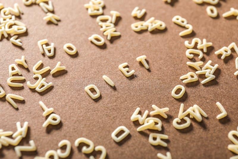 Wort DIÄT gemacht von den Teigwarenbuchstaben auf Farbhintergrund lizenzfreies stockbild