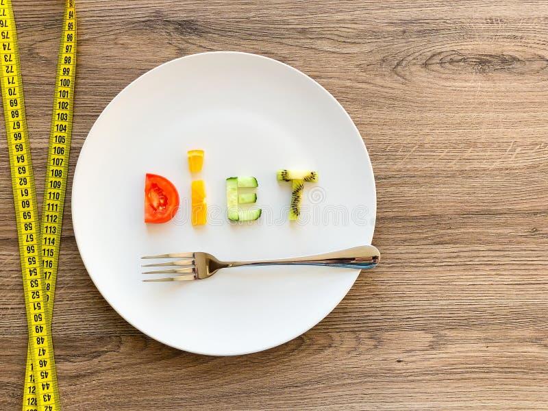 Wort DIÄT gemacht von geschnittenem Gemüse in der Platte mit dem Messen auf hölzernem Hintergrund lizenzfreies stockbild