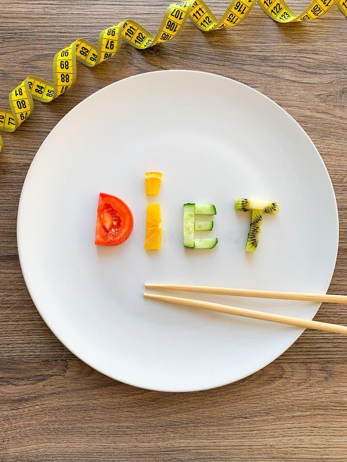 Wort DIÄT gemacht von geschnittenem Gemüse in der Platte mit dem Messen auf hölzernem Hintergrund stockbilder