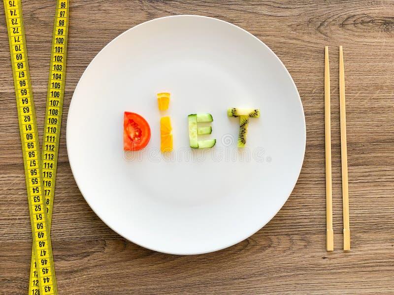 Wort DIÄT gemacht von geschnittenem Gemüse in der Platte mit dem Messen auf hölzernem Hintergrund stockfotografie