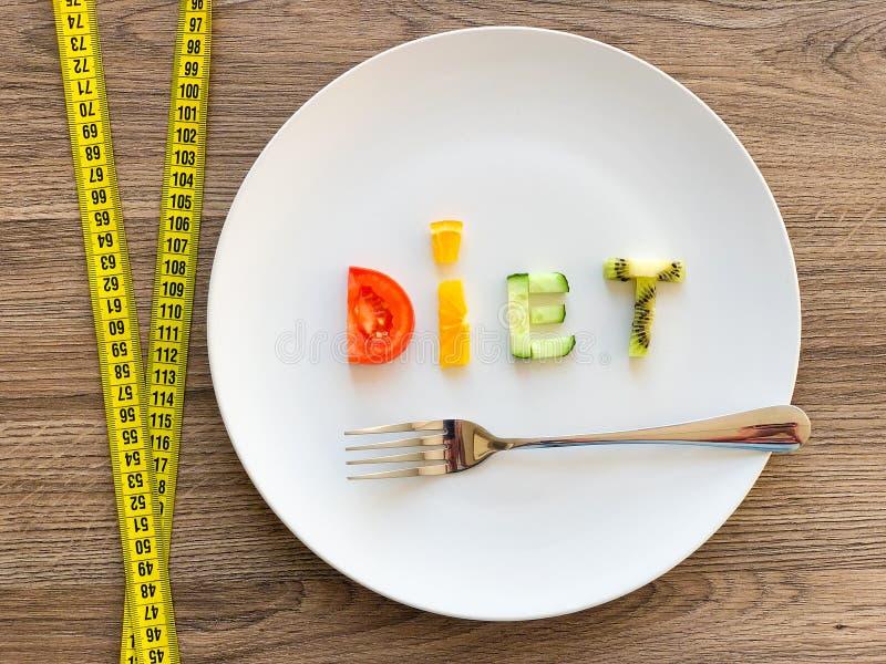 Wort DIÄT gemacht von geschnittenem Gemüse in der Platte mit dem Messen auf hölzernem Hintergrund stockfotos