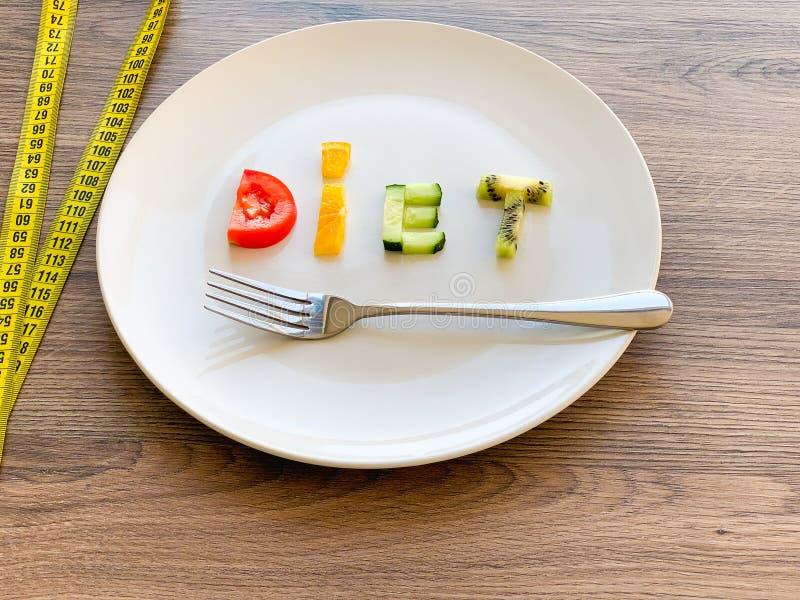 Wort DIÄT gemacht von geschnittenem Gemüse in der Platte mit dem Messen auf hölzernem Hintergrund stockbild