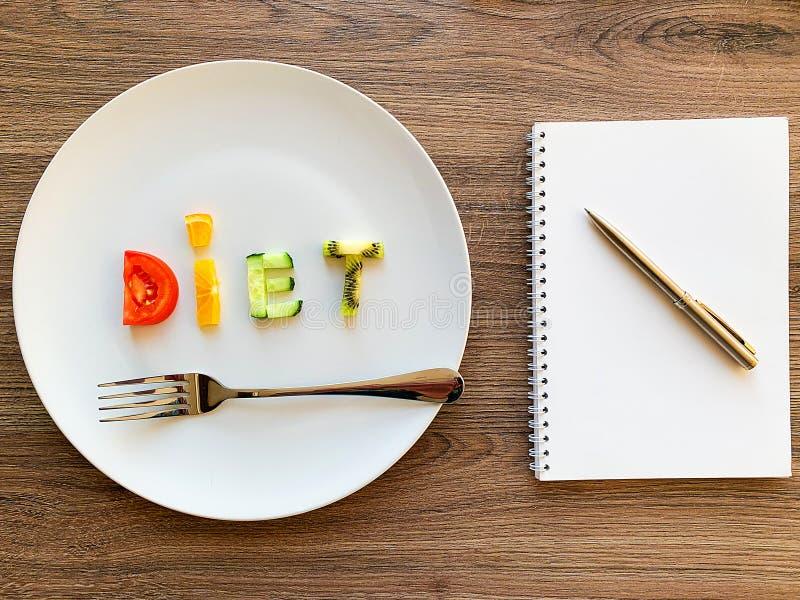 Wort DIÄT gemacht von geschnittenem Gemüse im weißen Platten- und Diätplan auf hölzernem Hintergrund lizenzfreie stockfotografie