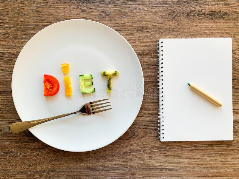 Wort DIÄT gemacht von geschnittenem Gemüse im weißen Platten- und Diätplan auf hölzernem Hintergrund lizenzfreies stockfoto