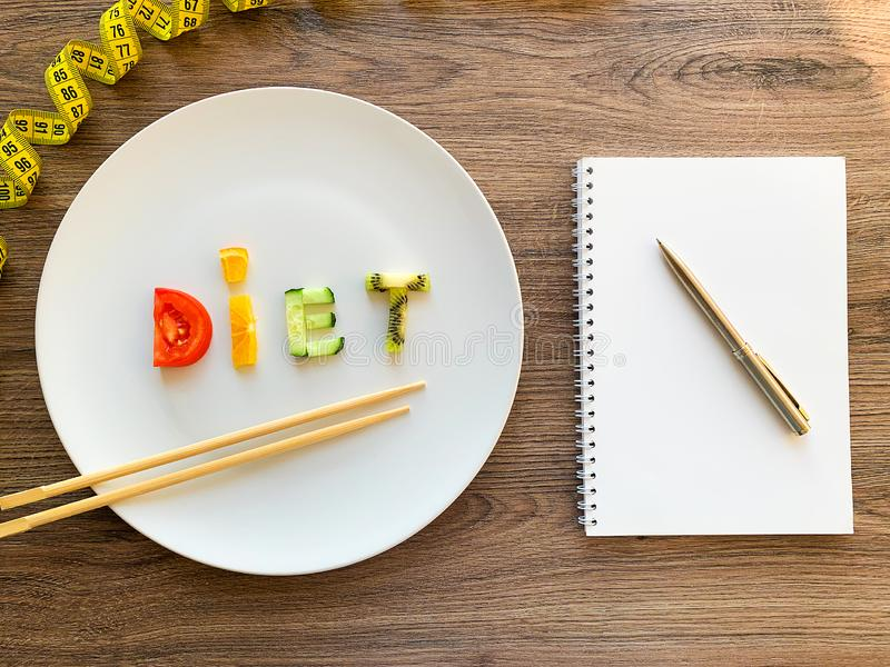 Wort DIÄT gemacht von geschnittenem Gemüse im weißen Platten- und Diätplan auf hölzernem Hintergrund stockbilder