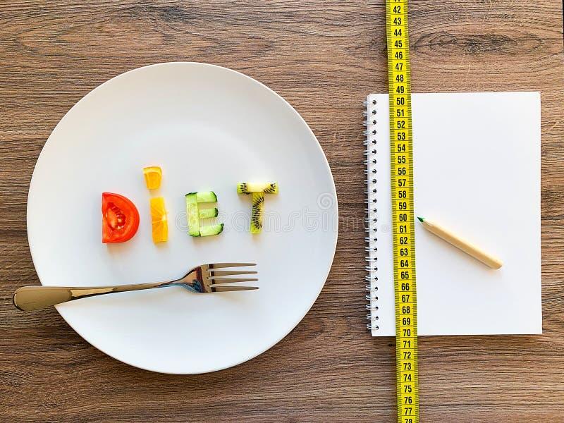 Wort DIÄT gemacht von geschnittenem Gemüse im weißen Platten- und Diätplan auf hölzernem Hintergrund stockfotos