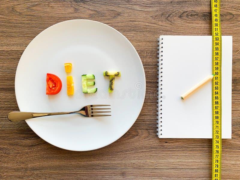 Wort DIÄT gemacht von geschnittenem Gemüse im weißen Platten- und Diätplan auf hölzernem Hintergrund lizenzfreie stockfotos
