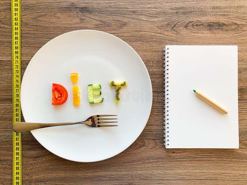 Wort DIÄT gemacht von geschnittenem Gemüse im weißen Platten- und Diätplan auf hölzernem Hintergrund stockfotografie