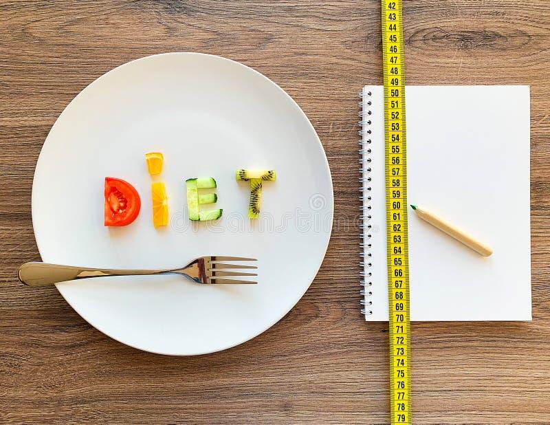 Wort DIÄT gemacht von geschnittenem Gemüse im weißen Platten- und Diätplan auf hölzernem Hintergrund stockfoto