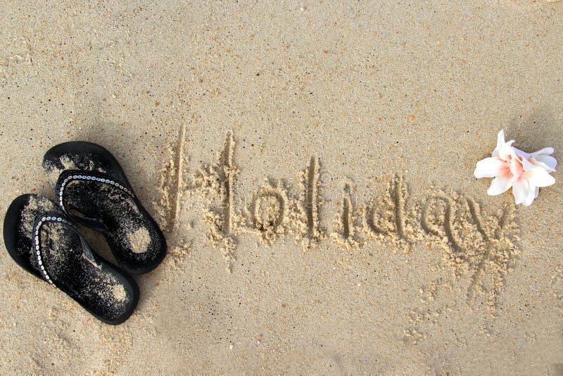 Wort-Feiertag geschrieben auf den nassen Sand lizenzfreie stockfotografie