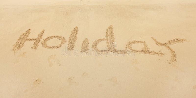Wort-Feiertag geschrieben auf nass Strandsand stockbild