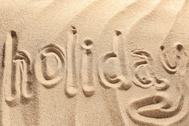 Wort FEIERTAG geschrieben auf Strandsand stockfotos