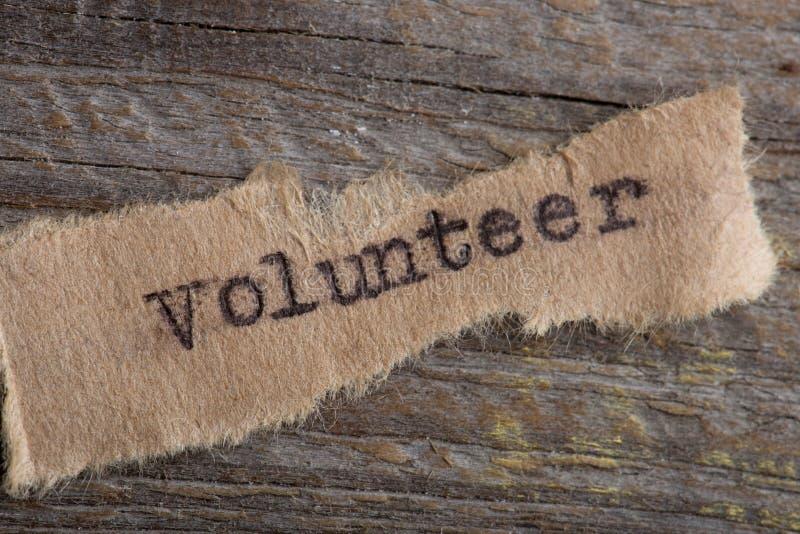 Wort-Freiwilliger geschrieben auf einem Stückchen Papier auf Weinleseschreibmaschine stockfotografie
