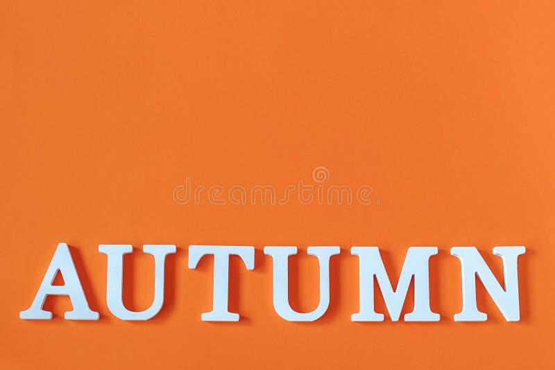 Wort-Herbst von den weißen Buchstaben mit Kopienraum auf orange Papierhintergrund, minimale Art Konzepthallo Fall Kreative Draufs stockfoto