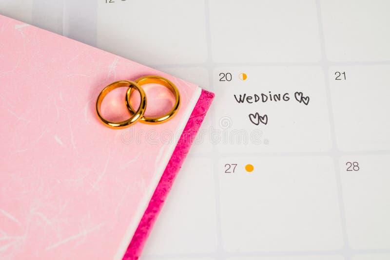 Wort-Hochzeit zum Anzeigen-Hochzeitstag mit Ehering auf Kalenderplanung lizenzfreie stockfotos