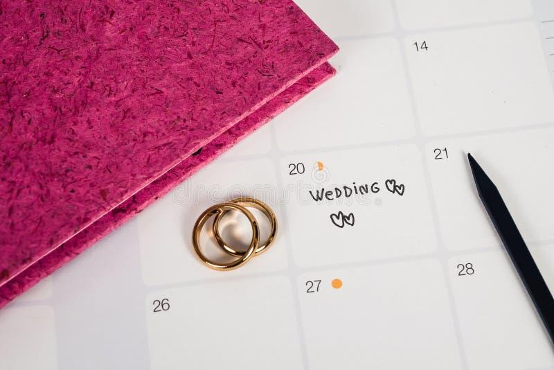 Wort-Hochzeit zum Anzeigen-Hochzeitstag mit Ehering auf Kalenderplanung stockfoto