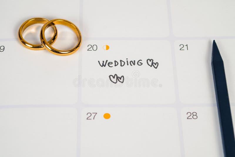 Wort-Hochzeit zum Anzeigen-Hochzeitstag mit Ehering auf Kalenderplanung lizenzfreies stockbild
