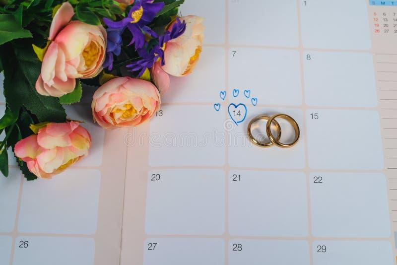 Wort-Hochzeit zum Anzeigen-Hochzeitstag mit Ehering auf Kalenderplanung lizenzfreie stockfotografie