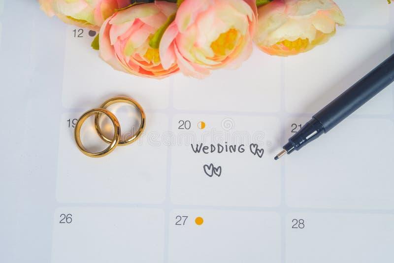 Wort-Hochzeit zum Anzeigen-Hochzeitstag mit Ehering auf Kalenderplanung lizenzfreie stockbilder