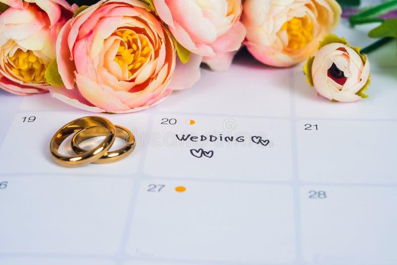 Wort-Hochzeit zum Anzeigen-Hochzeitstag mit Ehering auf Kalenderplanung stockbild