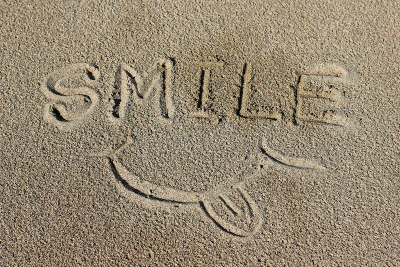Wort-Lächeln auf dem Sand stockbild