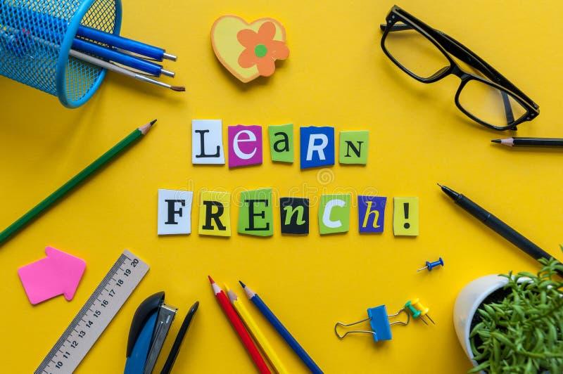 Wort LERNEN FRANZÖSISCH, das mit geschnitzten Buchstaben auf gelbem Schreibtisch mit Büro oder Schulbedarf, Briefpapier gemacht w stockbild