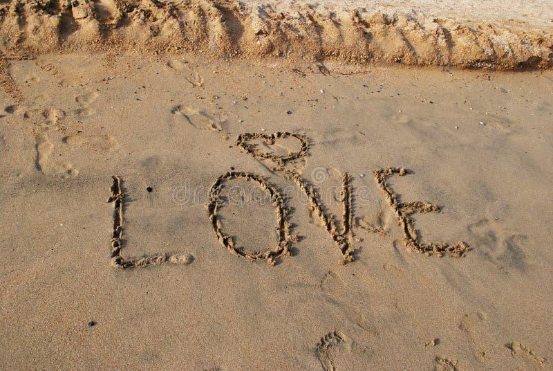 Wort LIEBE auf nassem Sand stockfotos