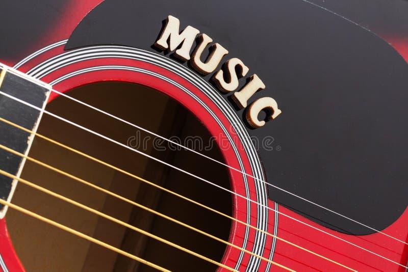 Wort-Musik mit hölzernen Buchstaben, Nahaufnahme auf einer Oberfläche der roten Akustikgitarre Musikunterhaltungshintergrund lizenzfreie stockfotografie