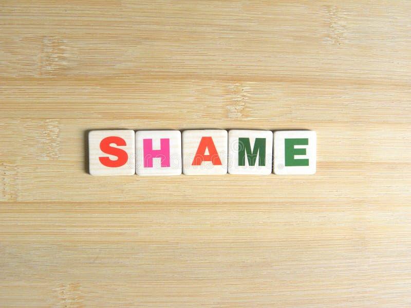 Wort-Schande auf hölzernem Hintergrund stockfotos