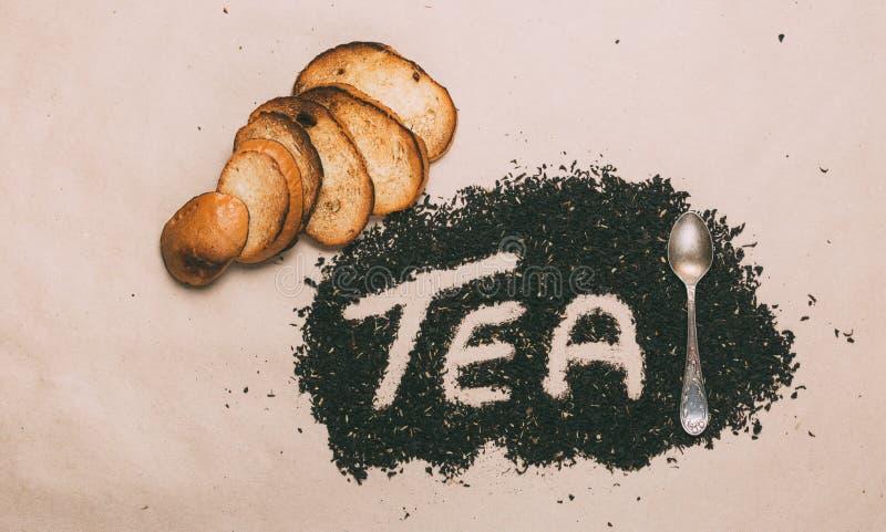 Wort-Tee wird mit kleinen Blättern schwarzer Tee, Toast und Teelöffel gemacht Beschneidungspfad eingeschlossen stockfotografie