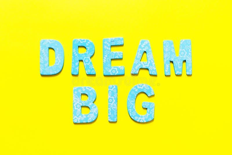 Wort TRÄUMEN GROSSES machte aus kleinem blauem hölzernem Buchstaben heraus auf gelbem b stockfoto