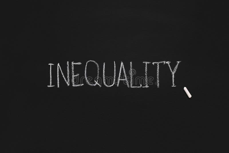 Wort-Ungleichheit geschrieben auf schwarzes Brett, Panorama stockfotografie