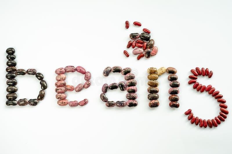 Wortbohnen ausgebreitet von zu den bunten Bohnen auf wei?em Hintergrund Gesundes Nahrungsmittelkonzept Beschneidungspfad eingesch lizenzfreie stockbilder