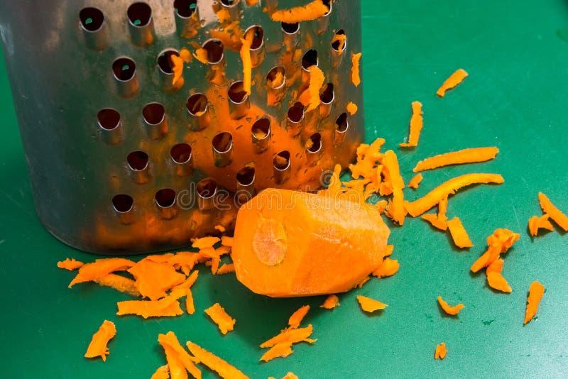 Wortel en geraspte wortel op een scherpe raad stock fotografie
