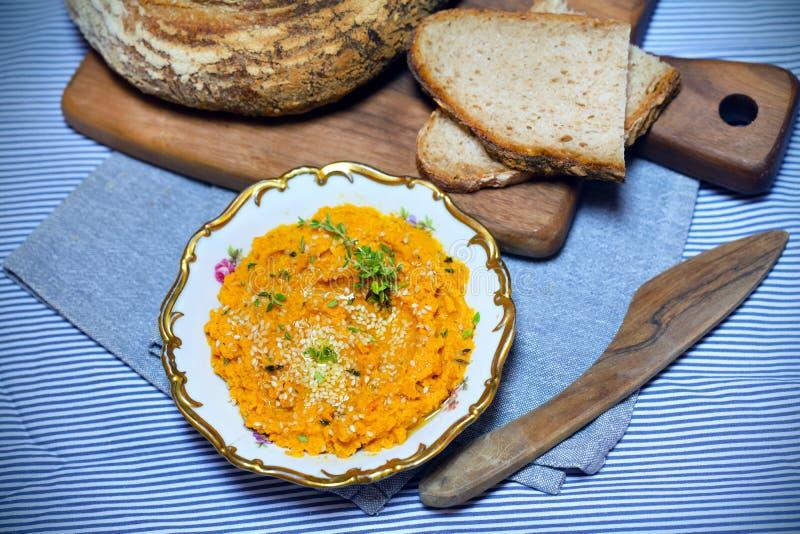 Wortel en pompoenonderdompeling, die met zuurdesembrood wordt uitgespreid royalty-vrije stock afbeeldingen