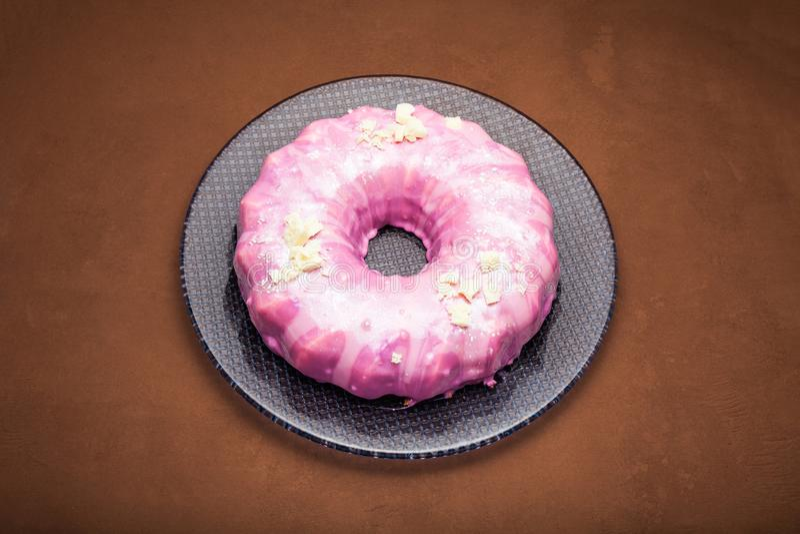 Wortelcake met roze suikerglazuur, witte chocolade en eetbaar zilver als ornament Een roze cake stock afbeelding