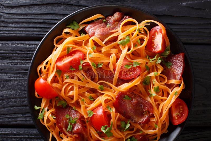 Worteldeegwaren met gebraden bacon, greens en tomatenclose-up op t stock afbeelding