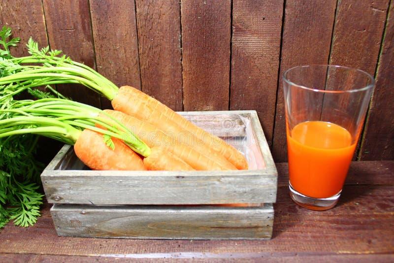 Wortelen en wortelsap stock afbeelding