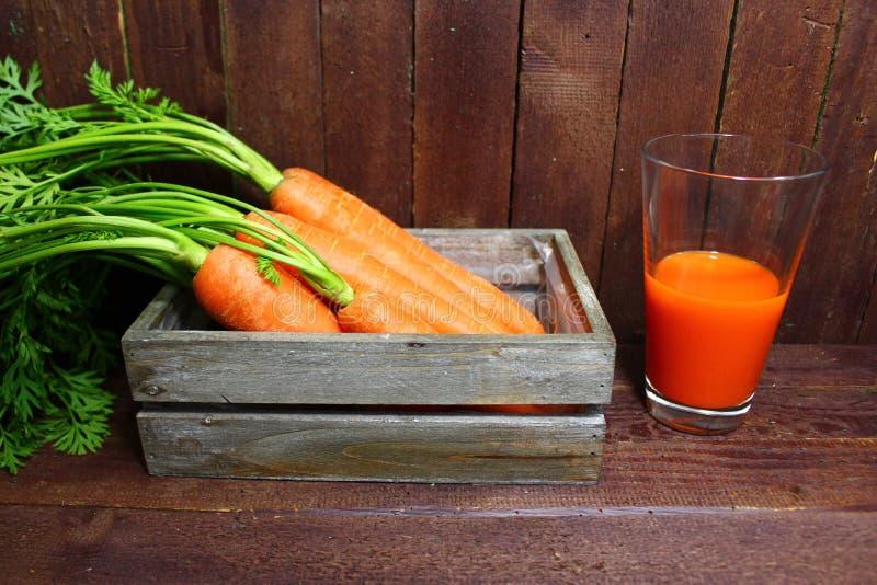 Wortelen en wortelsap stock afbeeldingen