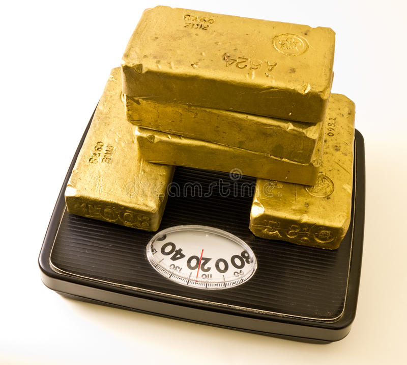 Worth Your Weight In Gold. So good your worth your weight in gold - a valuable individual. Five gold bars on a bathroom scale royalty free stock photography