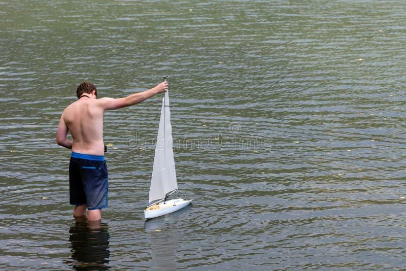 WORTHERSEE,奥地利,- 2018年8月5日:一个人在一个小湖遥控一个航行的游艇比例模型 图库摄影
