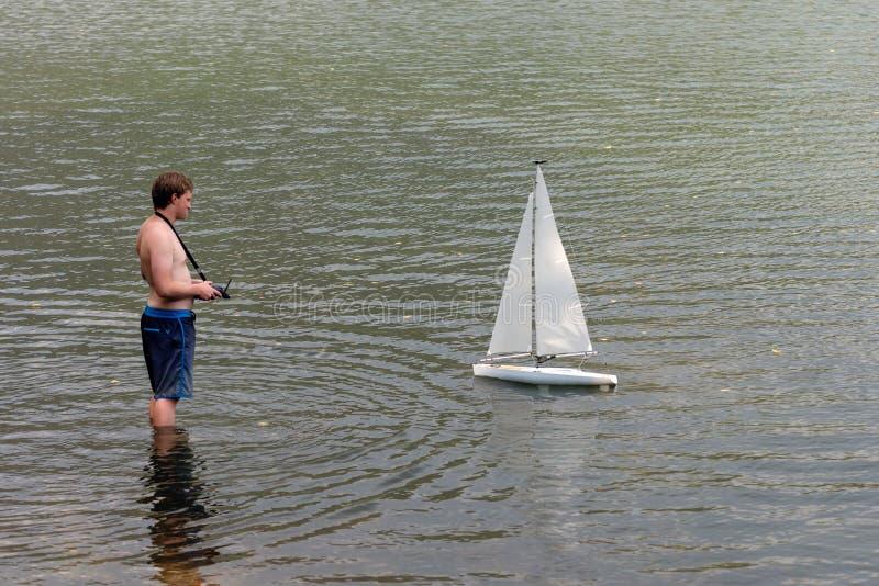 WORTHERSEE,奥地利,- 2018年8月5日:一个人在一个小湖遥控一个航行的游艇比例模型 库存图片