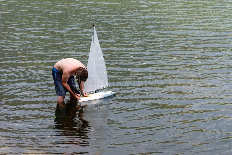 WORTHERSEE,奥地利,- 2018年8月5日:一个人在一个小湖遥控一个航行的游艇比例模型 免版税库存图片