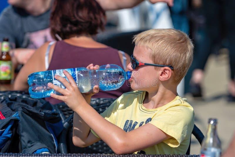 WORTHERSEE, ÖSTERREICH - 8. AUGUST 2018: Ein blonder Junge an einem heißen Tag trinkt Wasser von einer Plastikflasche lizenzfreies stockfoto