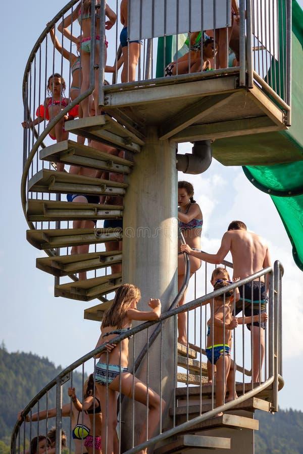 WORTHERSEE, ÖSTERREICH - 7. AUGUST 2018: Leute, welche die Leiter zum Wasserpark-Diaanfang klettern stockfotografie
