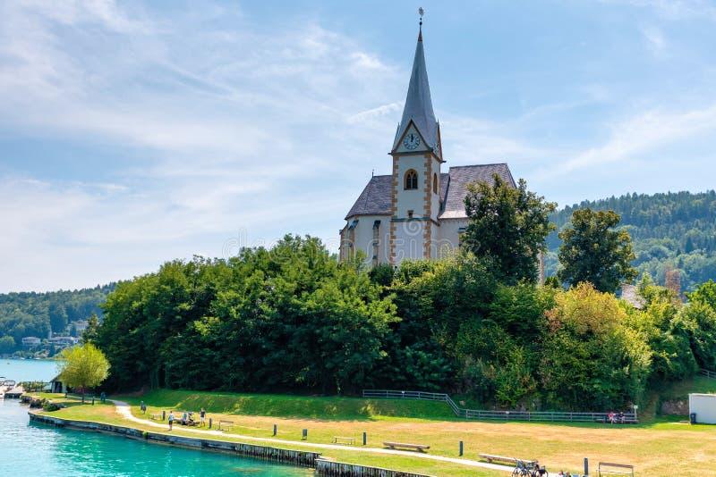WORTHERSEE ÖSTERRIKE - AUGUSTI 08, 2018: Sikt av Worthersee sjön med den Maria Worth kyrkan, Carinthia, Österrike royaltyfri bild
