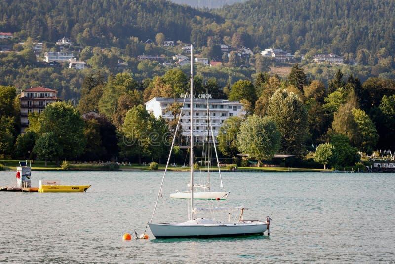 WORTHERSEE AUSTRIA, SIERPIEŃ, - 07, 2018: Wielka sceneria od łodzi brzeg linia jezioro, piękni budynki, góry, obrazy stock