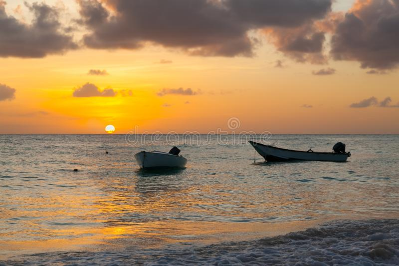 Worthing beach in Barbados at sunset. Two boats in the foreground. Carribean sea royalty free stock photos